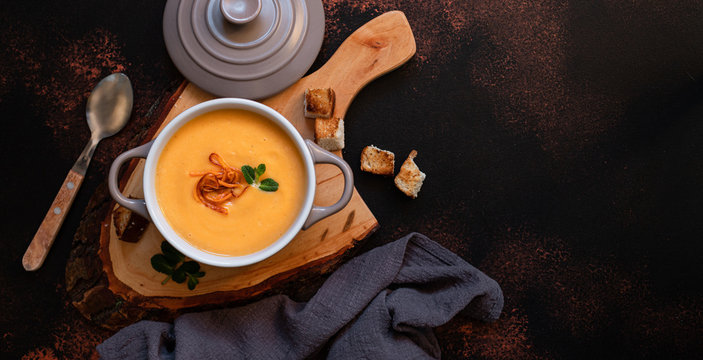 Cream sweet potato soup with sweet potato chips, breadcrumbs and herbs served in vintage copper plates on a vintage tray on a dark background. Vegetarian cream soup, healthy food. Top view, copy space