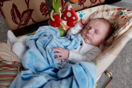 Cute baby sleeping in bouncer