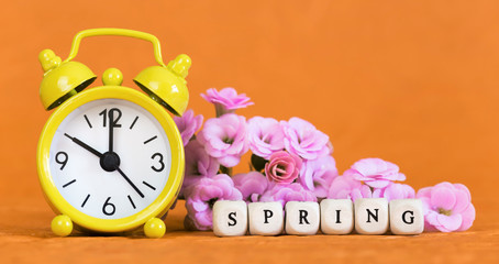 Spring forward, springtime, daylight savings time concept, yellow alarm clock and flowers on orange background. Copy space.