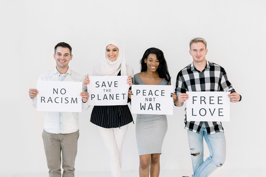 Photo of four cheerful young multiracial friends posing isolated over white background, holding paper sheets with no racism, no war, save the planet text. The concept of peace on earth, equality