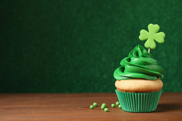 Delicious decorated cupcake on wooden table, space for text. St. Patrick's Day celebration