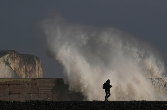 A man views large waves at as they hit the harbour wall at Newhaven, southern Britain