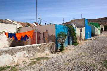 Street with colorful hanging football laundry and houses in Cape Verde