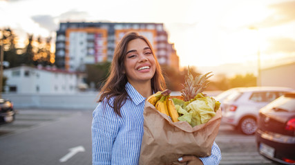 Cheerful woman carrying grocery bag while walking on street. Young beautiful woman smiling holding a paper bag full of groceries. Woman with a bag of groceries shopping