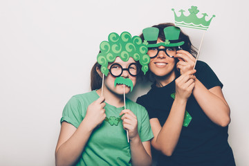 Young girl and a woman are preparing for the St Patricks Day party with photo booth props, Ireland traditional holiday, 17 March