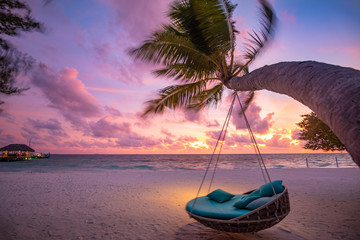 Wall Mural - Tropical sunset beach background as summer landscape panorama with beach swing or hammock and white sand and calm sea beach banner. Perfect beach scene vacation or summer holiday concept
