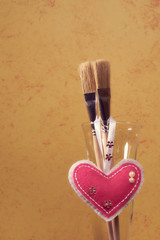 """Brushes on a painted wall background. Decorative plaster. Abstract ornament. Soft toy """"Heart"""". Handmade."""
