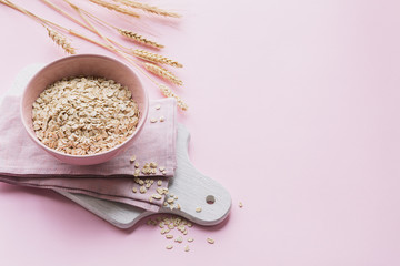 Bowl of dry oatmeal with ears of wheat on light background