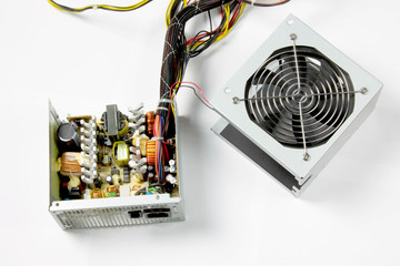 Disassembled computer power supply on white background