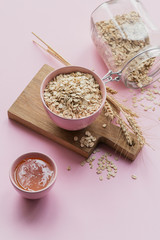 Bowl of dry oat flakes with honey and ears of wheat on light pink background