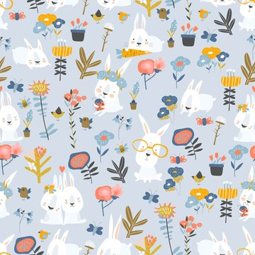 Seamless pattern of cute cartoon bunnies and color flowers on blue background