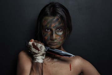 Young woman with camouflage face paint and knife in her hand