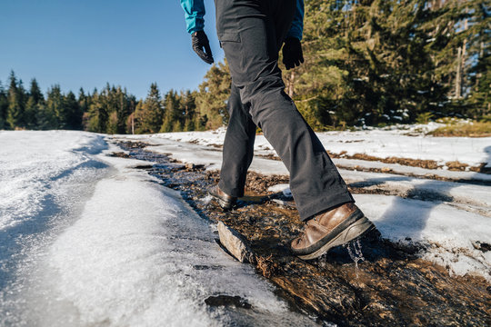 Trekking or hiking on a wet trail. Close up shot of hiking boots or shoes. Outdoor path with snow and water. Detail photo of outdoor hiking boots.