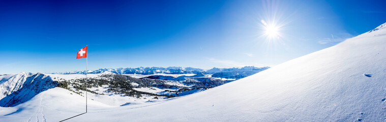 Fotobehang Alpen snow covered swiss alps mountain range with swiss national flag against blue sky, with copy space