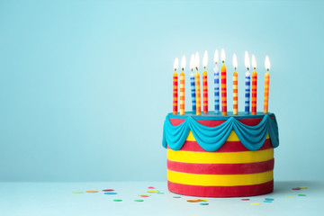 Fototapete - Brightly colored birthday cake with candles