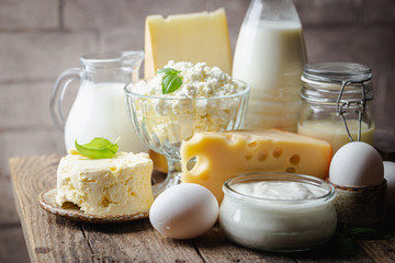 Fresh dairy products, milk, cottage cheese, eggs, yogurt, sour cream and butter on wooden table - fototapety na wymiar