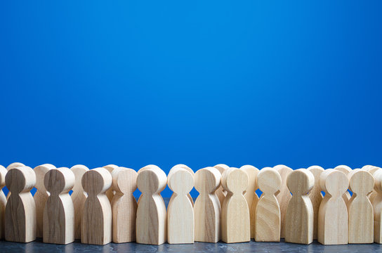 A crowd of wooden figures of people. Customers and buyers, statistics, preferences of Population. group of citizens, rally, political movement or electorate. Society, demography. Employees. Copy space