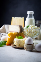 Fototapeten Milchprodukt Fresh dairy products, milk, cottage cheese, eggs, yogurt, sour cream and butter on white table, black background
