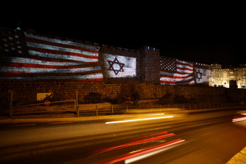 Cars drive by as the U.S. and Israeli national flags are projected on a part of the walls surrounding Jerusalem's Old City