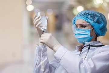 The doctor prepares a system for transfusion of infusion solutions .