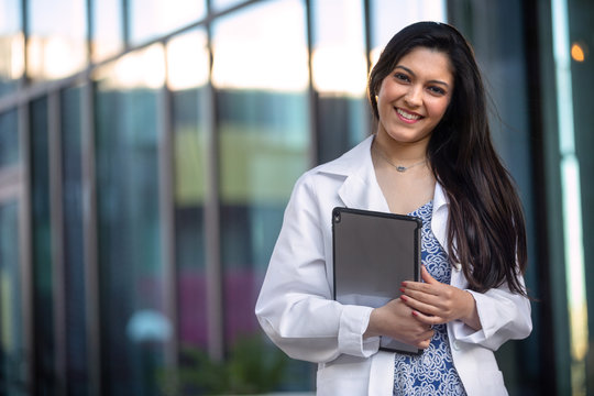 Portrait of a beautiful mixed ethnicity Hispanic Indian woman, medical professional, student, intern, or assistant at the workplace