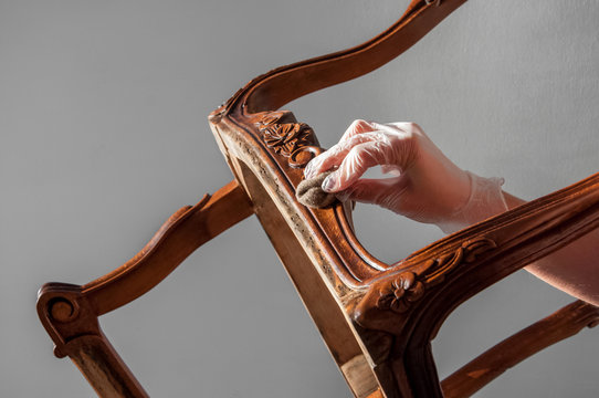 polishing furniture with hard wax oil and woolen cloth. all details back, armrest, leg. Repair of old furniture like an old Victorian old wooden armchair.
