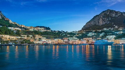 After sunset view of Marina Grande, Capri island, Italy. Illuminated streets of city are reflected in calm sea.