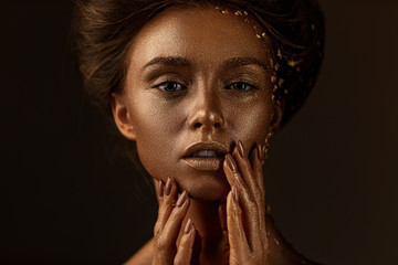 Fashion art portrait of model girl with holiday golden shiny professional makeup. beaty woman with gold metallic body and hair on dark background. Gold glowing skin.