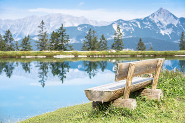 Mountain lake landscape view with bench in foreground
