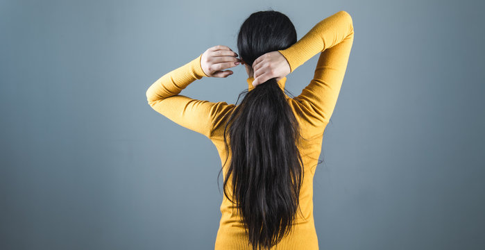 woman tie the hair on grey background