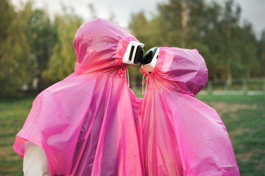 Closeup shot of two people in pink plastic raincoats and VR headset kissing each other