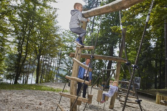 Little boy and a girl playing in the wooden playground during the daytime