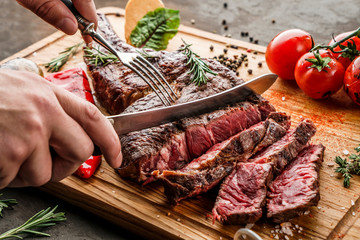 Hands cut grilled tomahawk meat medium rare or rib eye steak on wooden cutting board with grilled vegetables on dark background, close up
