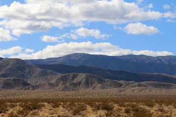 a blue cloudy sky with shadows on distant desert mountains