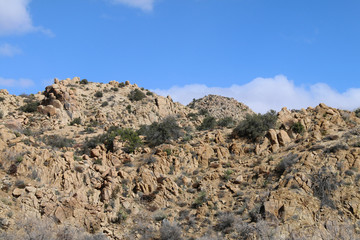 a blue sky and rocky hill ridge close-up