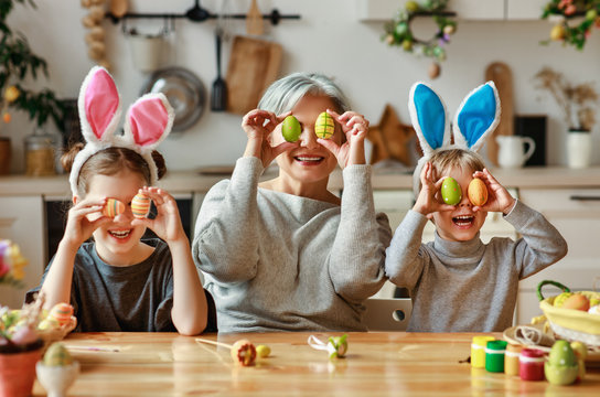 Happy easter! family   grandmother and children grandchildren paint eggs for holiday.