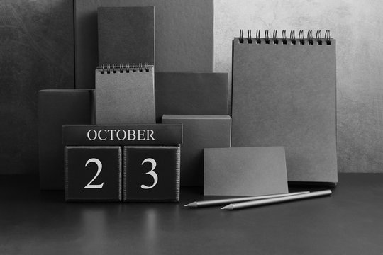 October 23th. Day 23 of month. Wood cube calendar with date month and day. Trendy classic black color. Lot of empty pages template for daily notes.