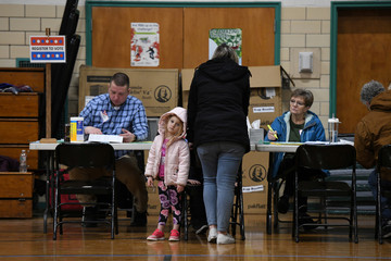 An unidentified little girl waits patiently at the polls in the Fairgrounds Middle School in New Hampshire's first-in-the-nation U.S. presidential primary election in Nashua