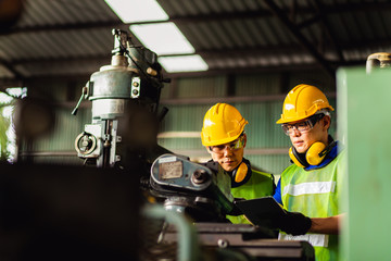 Two engineer working or recheck setup at industrial machinery in factory. Manual workers cooperating while measuring a electronic.