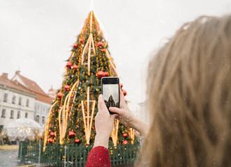 Crop view of woman taking photo of Christmas tree with smartphone on a snowy day