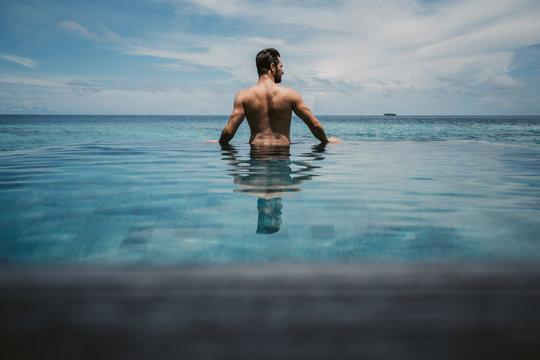 Rear view of man relaxing in infinity pool, Maguhdhuvaa Island, Gaafu Dhaalu Atoll, Maldives