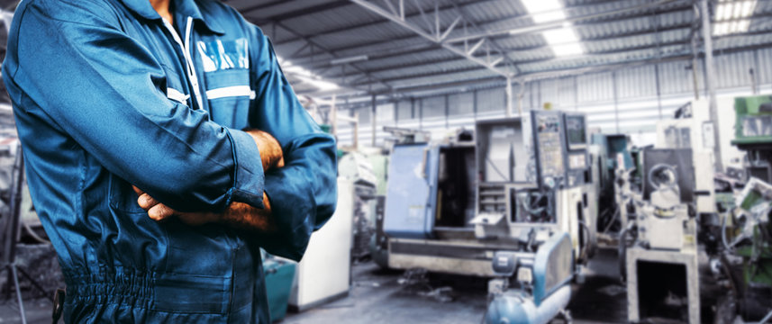 The image Engineer is wearing a uniform safety for industry background. men is standing with arms folded in a storage facility or warehouse.