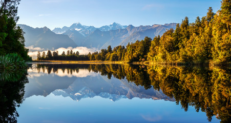New Zealand, Westland District, Fox Glacier, Lake Matheson reflecting surrounding forest and distant mountain range