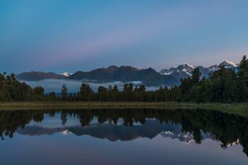 New Zealand, Westland District, Fox Glacier, Mountain range reflecting in Lake Matheson at dawn