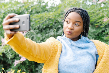 Portrait of young woman taking selfie with mobile phone