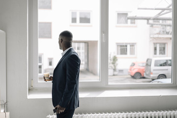 Businessman with paper cup and smartphone looking out of window