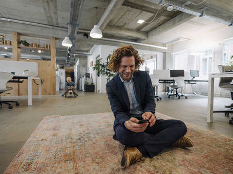 Businessman sitting on carpet in office using cell phone with son in background