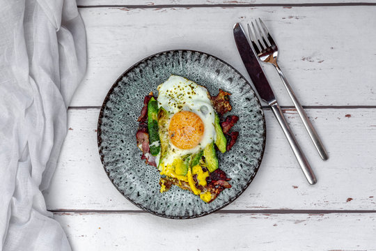 Fried egg with bacon, sliced avocado and Parmesan cheese