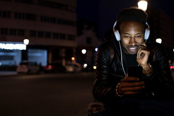 Man in the city at night with smartphone and headphones Wall mural