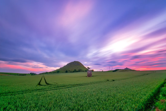 UK, Scotland, North Berwick, Purple clouds over green countryside field at dusk with North Berwick Law hill in background